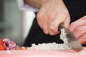 Chef cutting the onions on a wooden board